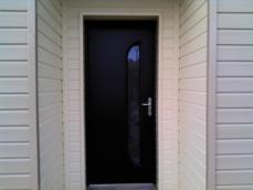 Porte d'entrée en alu noir sur maison en bois