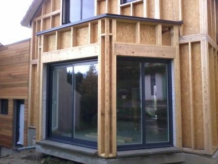 Pose des fenetres sur maison fabriquée en bois